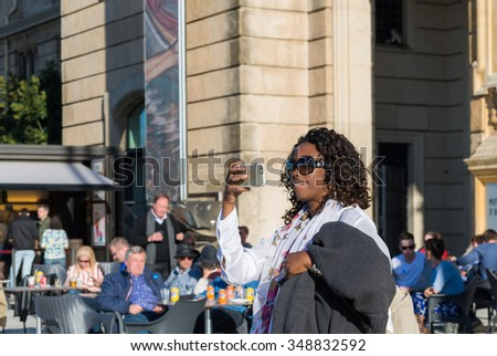 Attractive Brazilian tourist woman taking pictures with smartphone on sunny day.  Smiling girl wearing sunglasses and scarf shooting a photograph of famous landmark at sightseeing point in Europe - stock photo