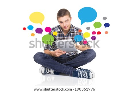 Attractive brunet teen boy in jeans and shirt sitting on floor with tablet. Colorful speech bubbles around him. Social network and internet concept. Isolated on white background. - stock photo