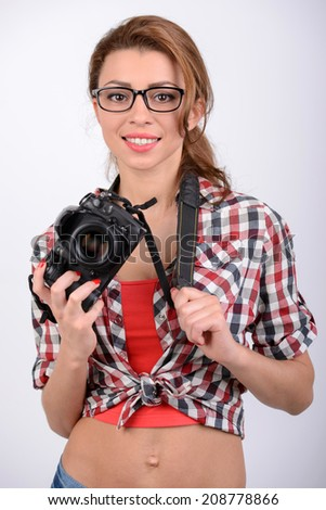 Attractive brunette aims her camera. composing a photograph in studio, isolated on white - stock photo