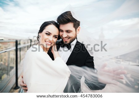 Attractive brunette bride and bridegroom standing close to each other at old city background and smiling, wedding photo, portrait.