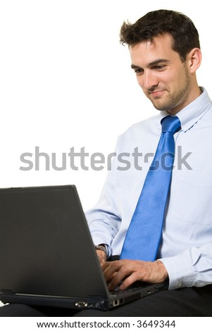 Attractive brunette business man sitting while working on a laptop computer wearing blue shirt and tie