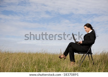 attractive brunette businesswoman relaxing on meadow - stock photo
