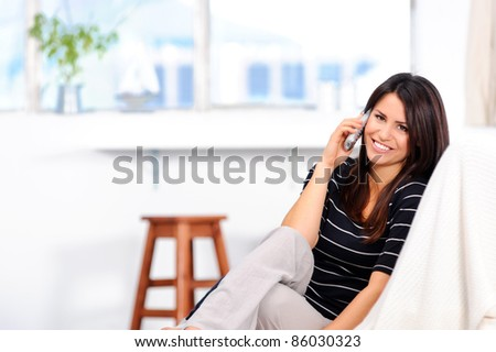 Attractive brunette chatting on the telephone at home - stock photo
