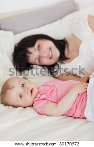 Attractive brunette female posing with her baby while lying on a bed in her apartment - stock photo