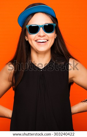 Attractive brunette girl in black blouse, blue cap and sunglasses, having fun, on a orange background, waist up - stock photo