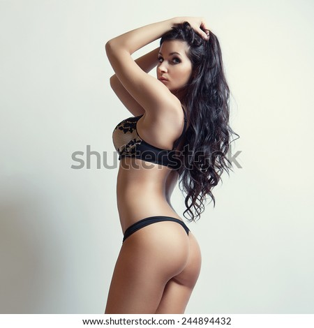 attractive brunette girl in black lingerie, cute butt - stock photo