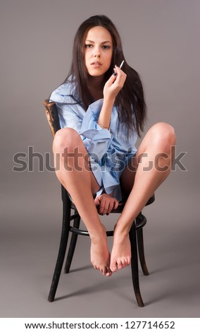 Attractive brunette girl with cigarette on chair at grey background - stock photo
