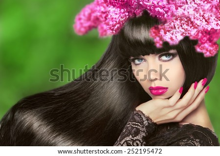 Attractive Brunette Girl with Flowers Long Hair. Healthy Black Hairstyle. Makeup. Manicured nails. Beauty Model Woman isolated on green natural background.