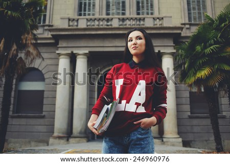 Attractive brunette hair student standing on university entrance background holding books - stock photo