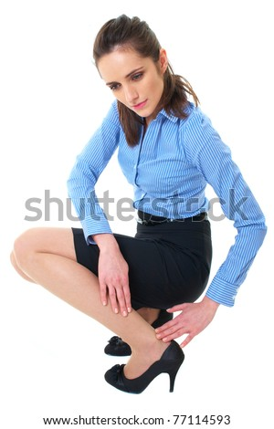 attractive brunette holds her calf, pain concept, wears blue shirt and pencil skirt, isolated on white - stock photo