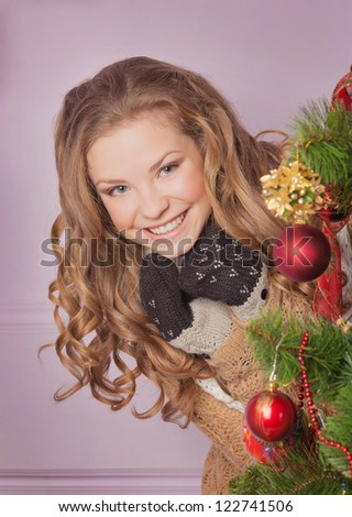 Attractive brunette in red Santa's cap looking out of Christmas tree - stock photo