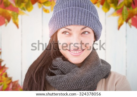 Attractive brunette looking up wearing warm clothes against autumn leaves on wood - stock photo