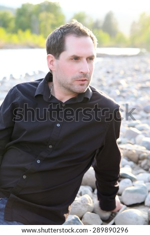 Attractive brunette male sitting on a pebble beach - stock photo