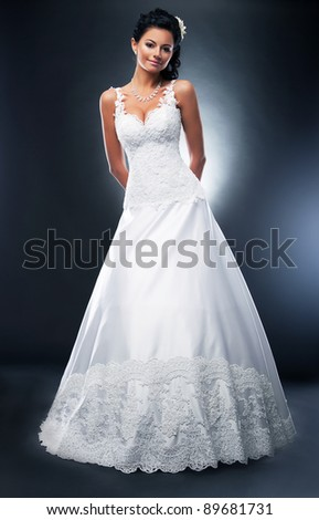 Attractive brunette model in white bridal dress with flower in her head posing in studio - stock photo