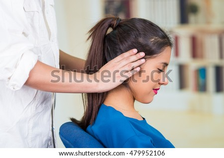 Attractive brunette office woman wearing blue sweater sitting by desk receiving head massage, stress relief concept