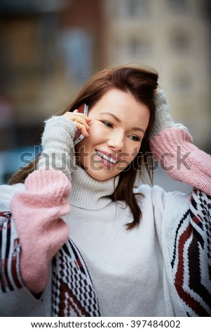 Attractive brunette talk over her mobile phone, street shoot with blurred background - stock photo