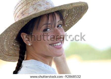 Attractive brunette wearing straw hat - stock photo