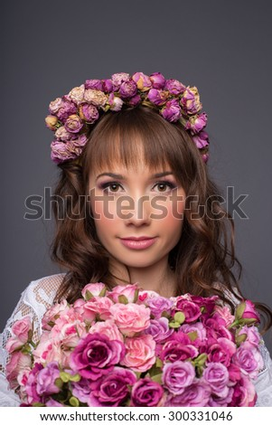 attractive brunette with a wreath of roses on her head. girl with a bouquet of roses in hands - stock photo