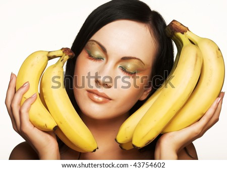 Attractive brunette with bananas on a white background
