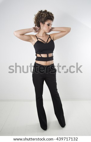 Attractive Brunette With Modern Hairstyle And Makeup Posing In Black Elegant Trousers And Sexy Black Shirt, Full Body Length Studio Shot Against White Background - stock photo