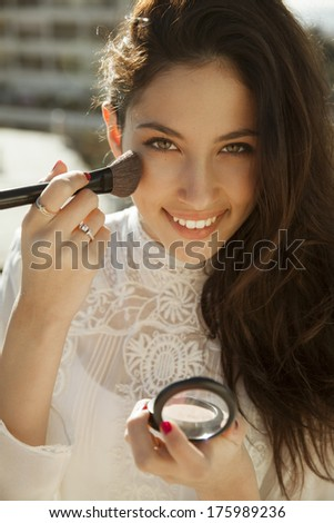 Attractive brunette woman doing make up .  - stock photo