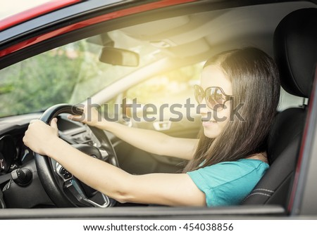 Attractive brunette woman driving a red car.  - stock photo