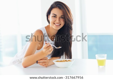 Attractive brunette woman eating bowl of cereal and smiling at the camera in the kitchen at home. - stock photo