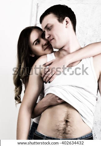 attractive brunette woman hugging a man looks out over his shoulder. woman takes off  man's shirt. sexual relationships between lovers
