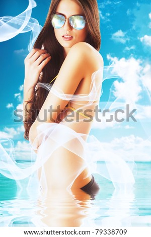 attractive brunette woman in white fabric on the beach in water - stock photo