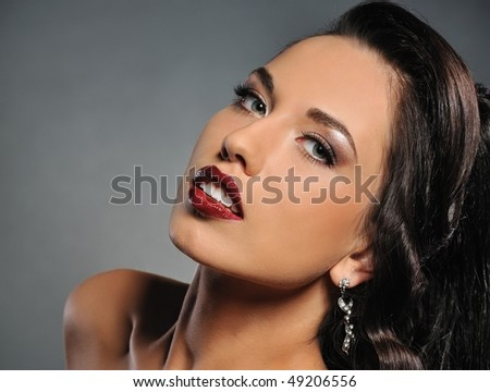 Attractive brunette woman isolated on grey background - stock photo