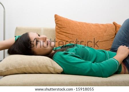 attractive brunette woman lying on sofa - stock photo