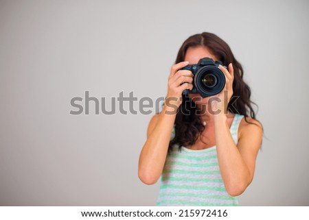 Attractive brunette woman-photographer takes pictures. Space for your text. - stock photo