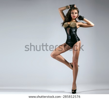 Attractive brunette woman posing in studio, wearing sexy black lingerie and gloves. Girl with slim legs. - stock photo