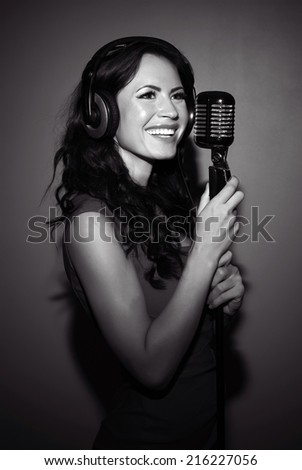 Attractive brunette woman recording a song in music studio. Black and white photo. - stock photo