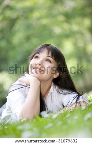 attractive brunette woman relaxing by lying on grass in park