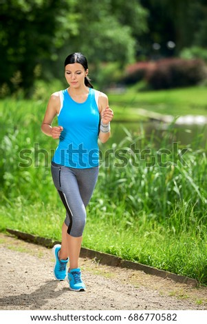 Attractive brunette woman running in outdoor park