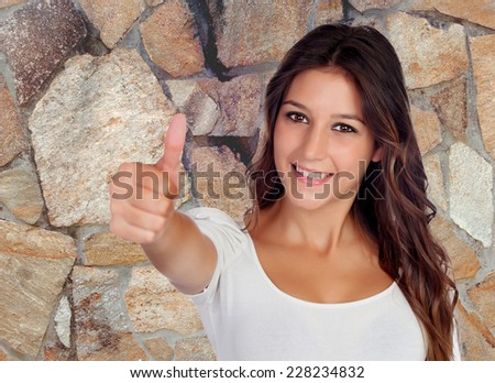 Attractive brunette woman saying Ok with a stone wall of background - stock photo