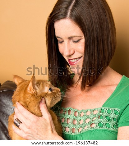 Attractive brunette woman smiling while holding a ginger cat - stock photo