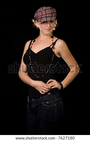 Attractive brunette woman wearing black top and funky hat on black