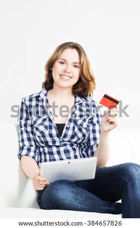 Attractive brunette woman with a credit card and a tablet computer.  - stock photo