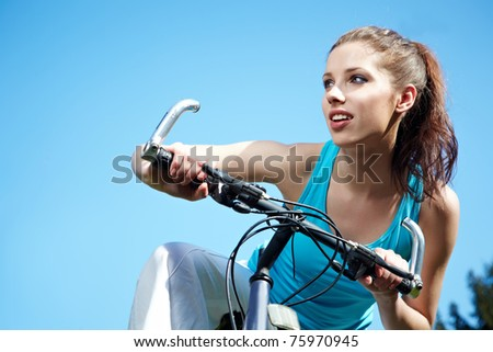 Attractive brunette woman with bike - stock photo