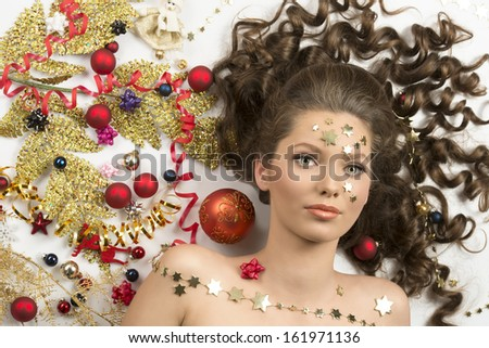 attractive brunette woman with curly hair posing in close-up beauty portrait surrounded by some christmas decorations. Red baubles, golden branch, ribbon and stars - stock photo