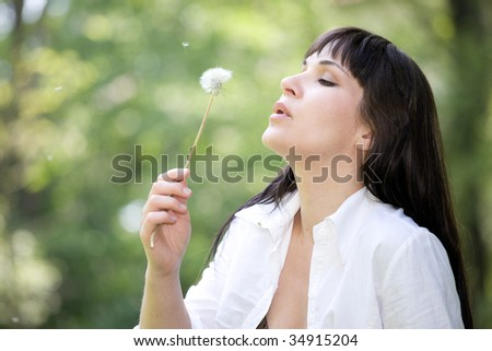 attractive brunette woman with dandelion in park - stock photo