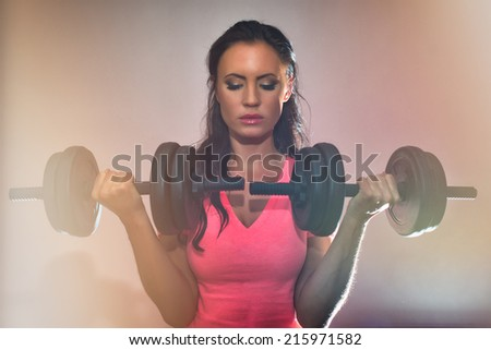 Attractive brunette woman working out with dumbbells. - stock photo