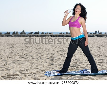 Attractive brunette woman works out on beach - wearing pink sports bra - standing on yoga mat with drinking from water bottle  - stock photo