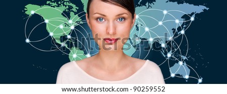 Attractive brunette young woman in futuristic interface standing in front of world map with glowing hot points location and connection lines.