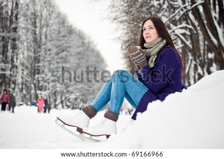 Attractive brunette young woman on the ice rink - stock photo