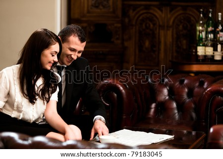 Attractive bunsiness couple smiling while is looking on a newspaper. Please see more images from the same shoot. - stock photo