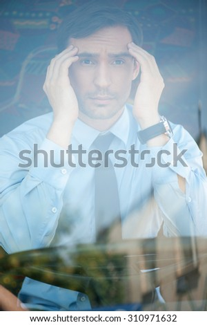 Attractive bus driver has pain in his head. He is touching his temples and looking forward sadly. The guy is sitting at steering wheel - stock photo