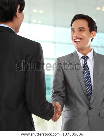 attractive business colleagues shaking hands and smiling